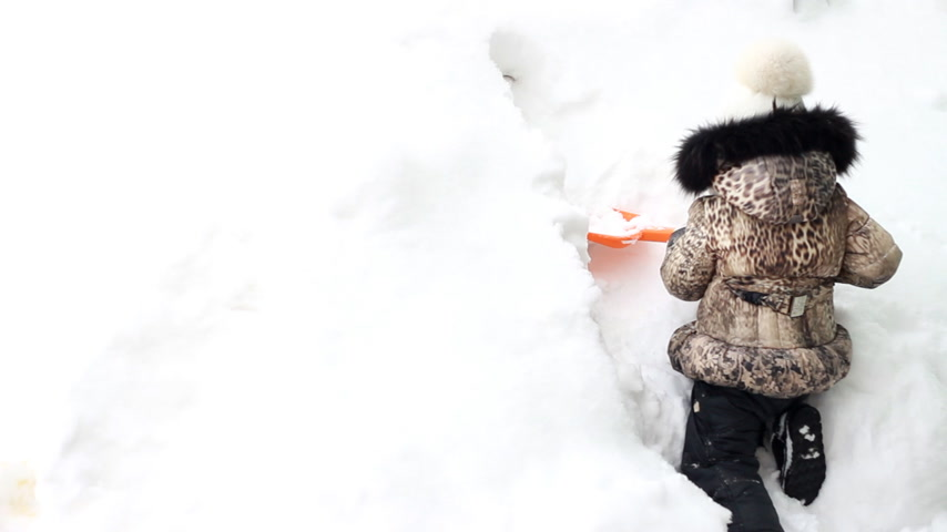 snow angel : Child girl is digging snow shovel. Very snowy winter and a lot of snow Stock Footage