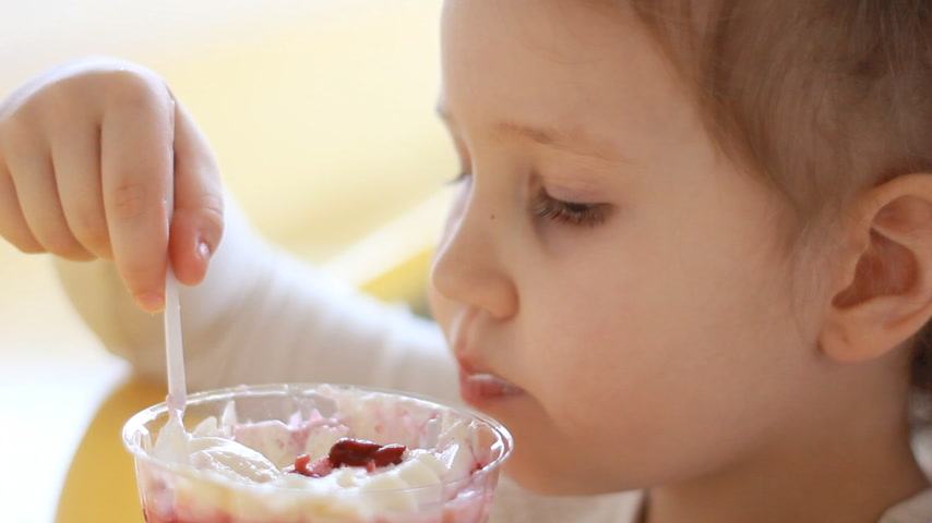 mastication : Child girl eating dessert in the cafe. Portrait of a baby who eats ice cream. Closeup Vidéos Libres De Droits