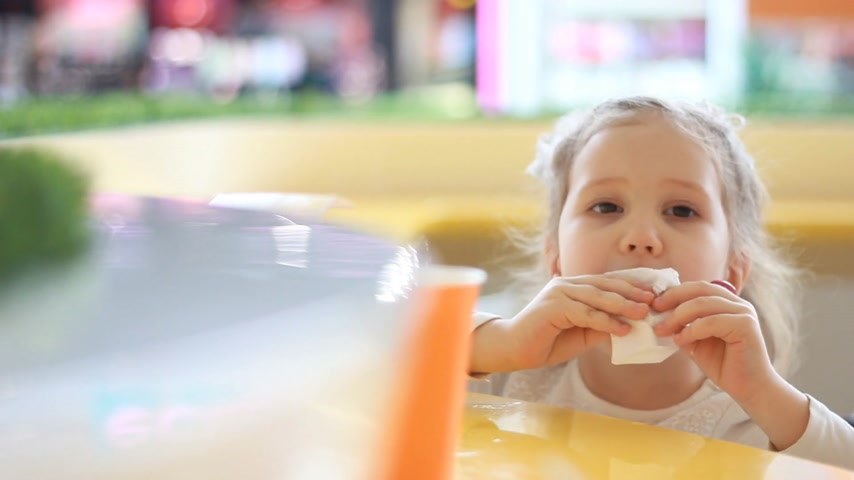 nibble : Baby girl eating nuggets in the cafe. Portrait child who eats fast food.