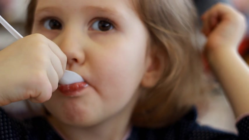 mors : Child eating dessert and drinking juice in the cafe. Portrait of a baby who eats ice cream. Stock Footage