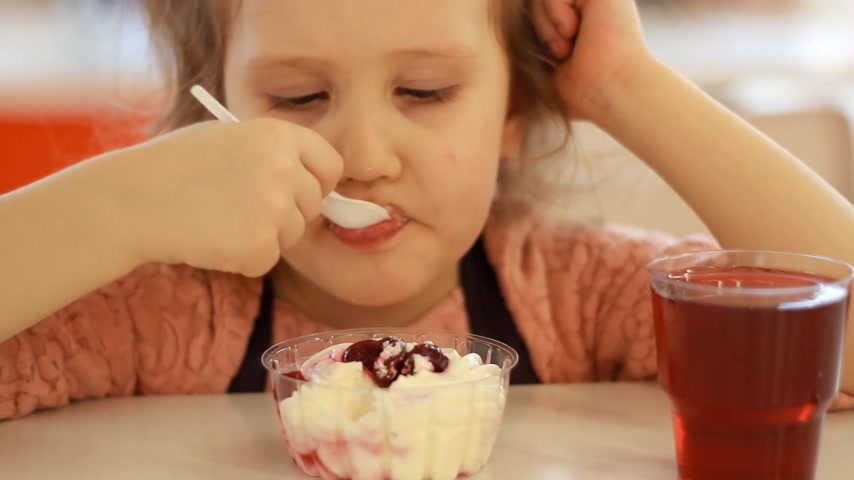 kompot : Child eating dessert and drinking juice in the cafe. Portrait of a baby who eats ice cream. Wideo