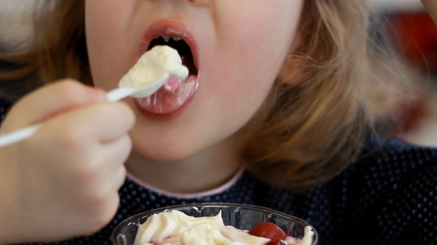 mors : Baby girl eating dessert and drinking juice in the cafe. Portrait of a child who eats ice cream Stock Footage