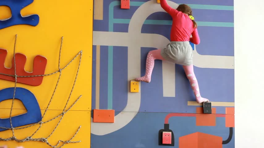 возможность : Child girl climbing up on an indoors climbing wall. Baby plays childrens sports games on the playground