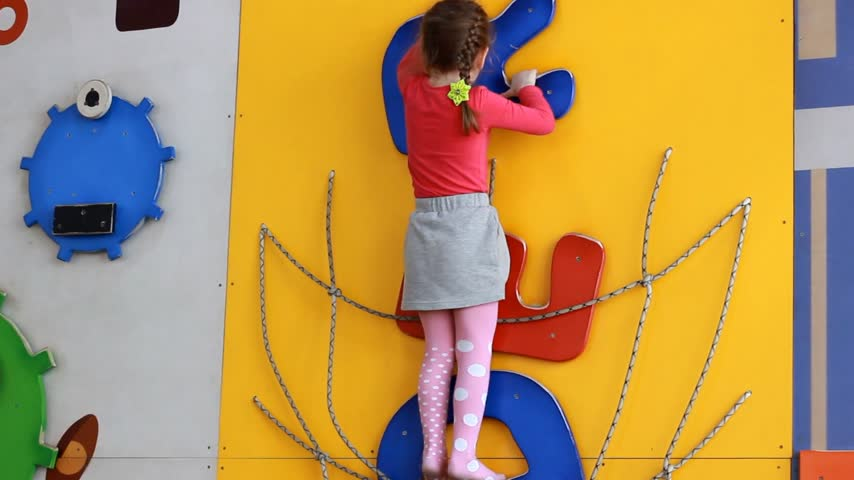 olasılık : Child girl climbing up on an indoors climbing wall. Baby plays childrens sports games on the playground