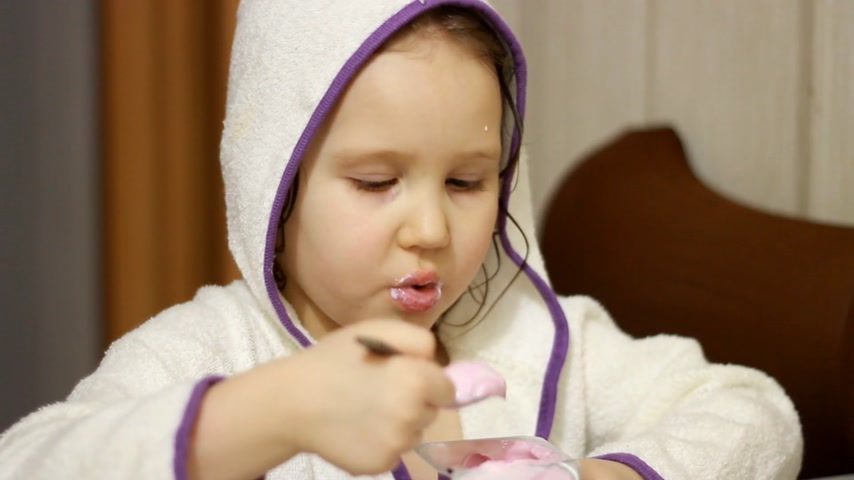 자신 : Baby girl eating cottage cheese with a spoon. Child eats dairy product yogurt. Portrait close-up