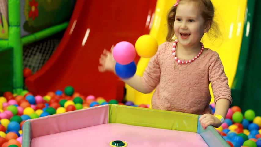 get out : Child girl playing on the playground with colorful balloons. Baby plays in the room for games