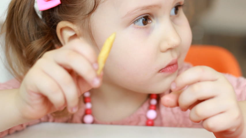 pepite : Child girl eating fast food french fries in a cafe. Portrait closeup Filmati Stock