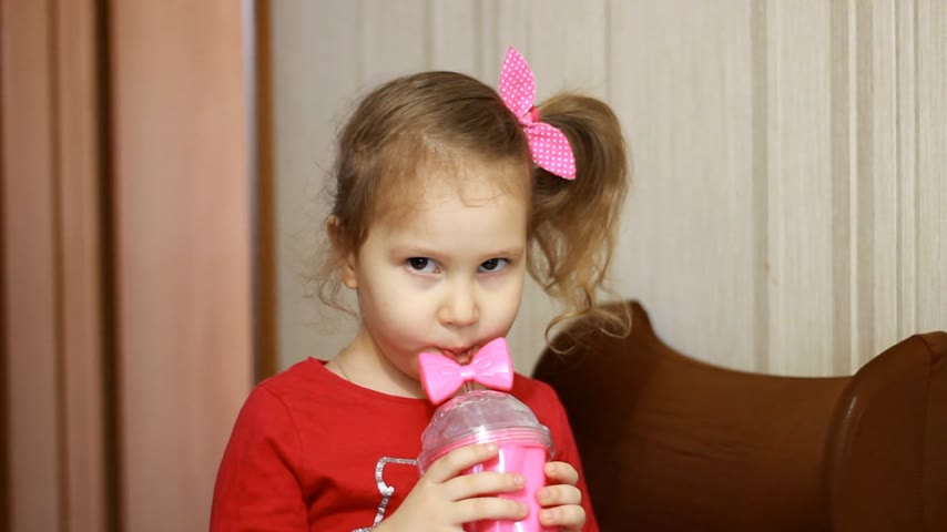 mors : Child girl drinking juice. Portrait of a baby who drinks drink