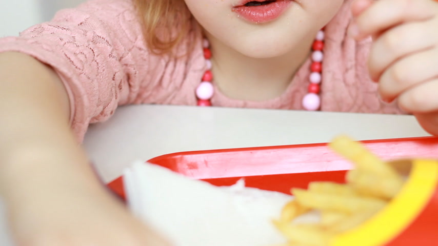 nibble : Baby girl eating fast food french fries in a cafe. Portrait closeup