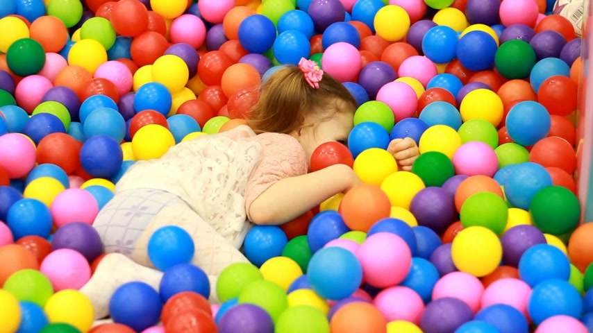entrar : Child girl playing on the playground with colorful balloons. Baby plays in the room for games. Archivo de Video