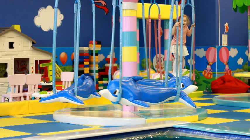 get out : Child girl playing on carousel on the playground. Baby plays in the room for games Stock Footage