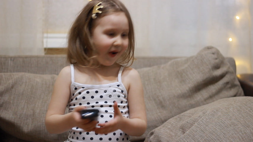 мультфильмы : Baby girl watching TV. Child turns on the television using the remote.