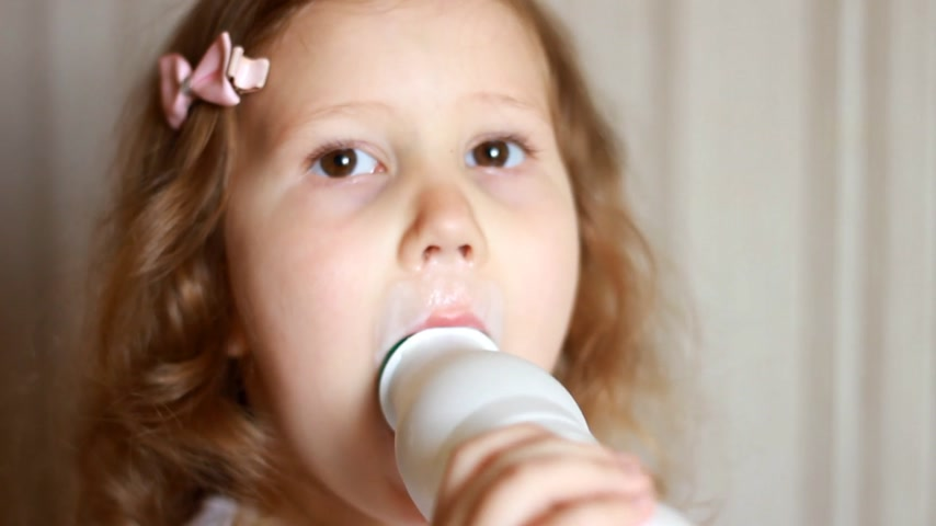 молочный : Baby girl drinking a milk drink from a bottle, kefir, dairy product. Child smiling and showing a white mustache from yogurt.