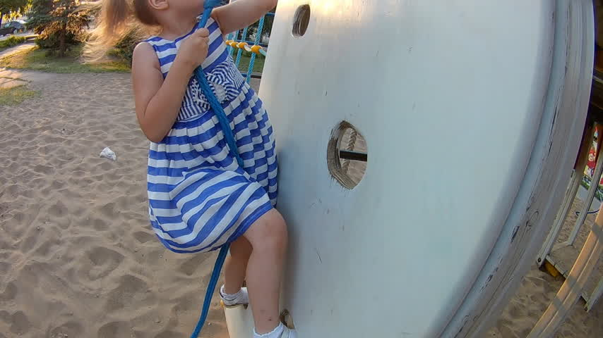 возможность : Child climbing up on climbing wall. Baby girl playing childrens sports games on the playground
