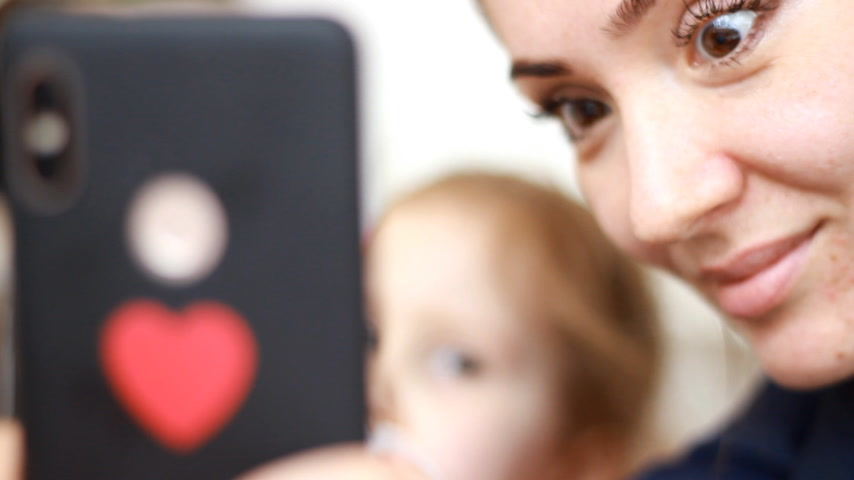 Closeup portrait of a woman and her baby with a mobile phone