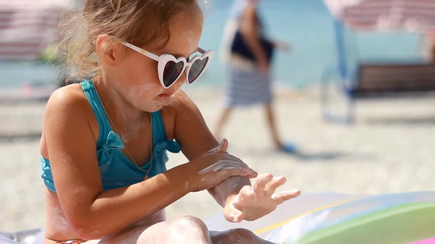 koruma : Child smearing sun cream fase and body. Sunburn. Suncream cream. Sunprotection cream. Cute baby girl in sunglasses sunbathes on a beach near the sea.
