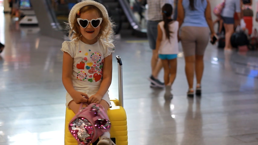 Baby girl tourist is sitting on a big yellow suitcase on train station. Child is waiting for departure on a trip at the airport. Waiting for travel.