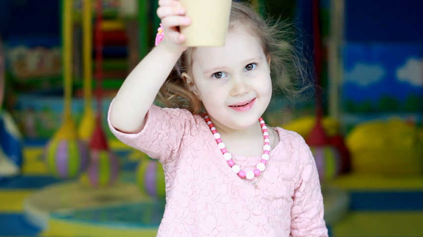 Child is drinking coffee. Close-up portrait of a cute baby girl who drinks a drink Filmati Stock