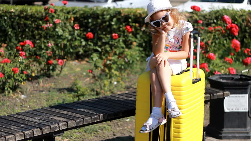 Child tourist with big yellow suitcase. Baby girl waiting for travel. Filmati Stock