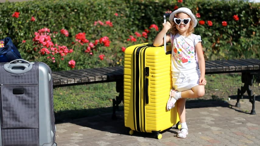 Child tourist with big yellow suitcase. Baby girl waiting for travel. Stock Footage