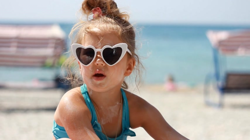 Baby girl smearing sun cream fase and body. Sunburn. Suncream cream. Sunprotection cream. Child in sunglasses sunbathes on a beach near the sea Stock Footage