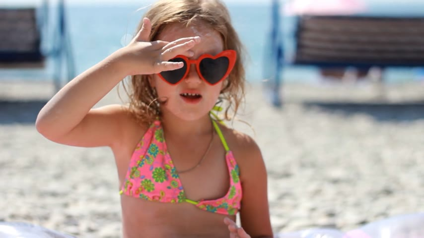 Baby girl smearing sun cream fase and body. Sunburn. Suncream cream. Sunprotection cream. Child in sunglasses sunbathes on a beach near the sea.