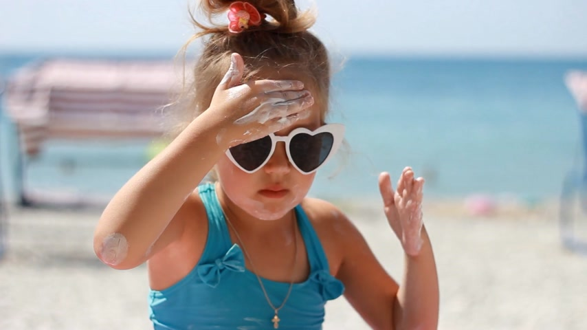 Child smearing sun cream fase. Sunburn. Suncream cream. Sunprotection cream. Cute baby girl in sunglasses sunbathes on a beach near the sea Filmati Stock