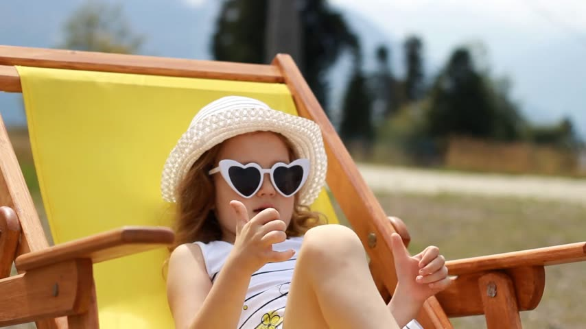 Portrait of joyful baby girl tourist happily showing thumbs. Child siting on the on a deck chair.
