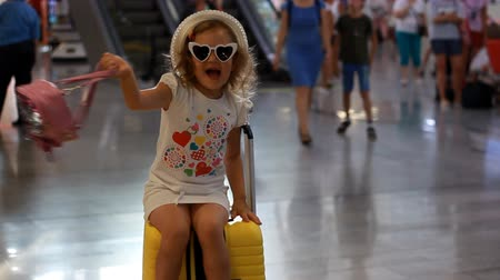 pasaport : Baby girl tourist is sitting on a big yellow suitcase on train station and waving hand goodbye. Child is waiting for departure on a trip at the airport. Waiting for travel