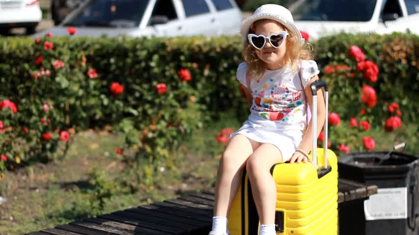 Baby girl tourist is sitting on a big yellow suitcase. Child waiting for travel.