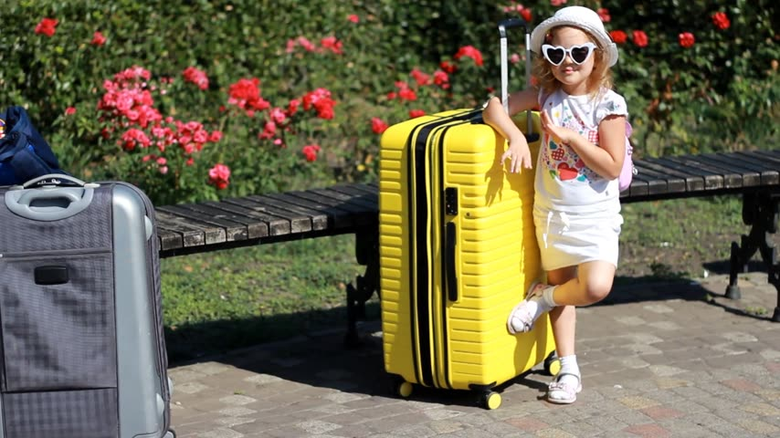 Baby girl tourist standing with a lot of luggage and waving hand goodbye. Child waiting for travel.
