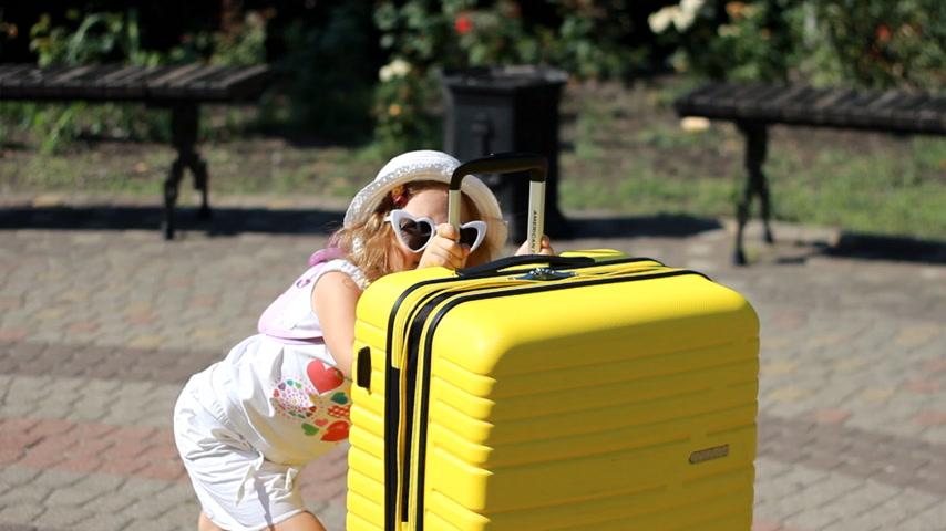 Heavy luggage. Child tourist with big yellow suitcase. Baby girl waiting for travel. Stock Footage