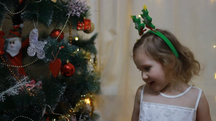 Baby girl in anticipation of Santa and a gift at Christmas. New Year and Christmas tree. Filmati Stock
