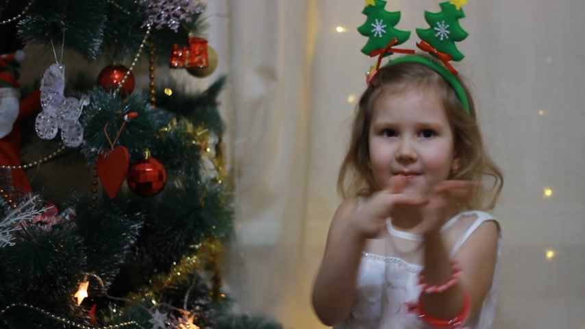 Applause. Baby clapping. Child girl in anticipation of Santa and a gift at Christmas. New Year and Christmas tree.