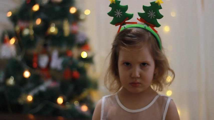 Sad and upset child girl in anticipation of Santa and a gift at Christmas. New Year and Christmas tree.