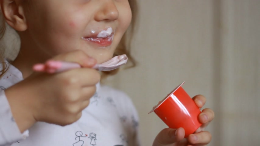 Baby girl eats dairy product yogurt. Child eating cottage cheese with a spoon. Portrait close up Stock Footage