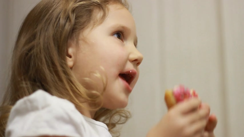 Child mouth bites rose donut. Closeup baby girl eating doughnut with glase. Delicious, sweet, sweettooth Stock Footage