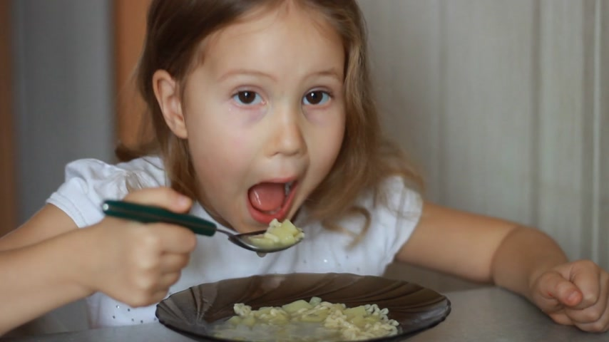 Delicious lunch. Closeup baby girl sitting at the table of home cooking and eating food. Child eats soup. Stock Footage