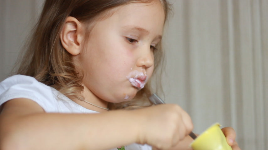 Baby girl eats dairy product yogurt. Child eating cottage cheese with a spoon.