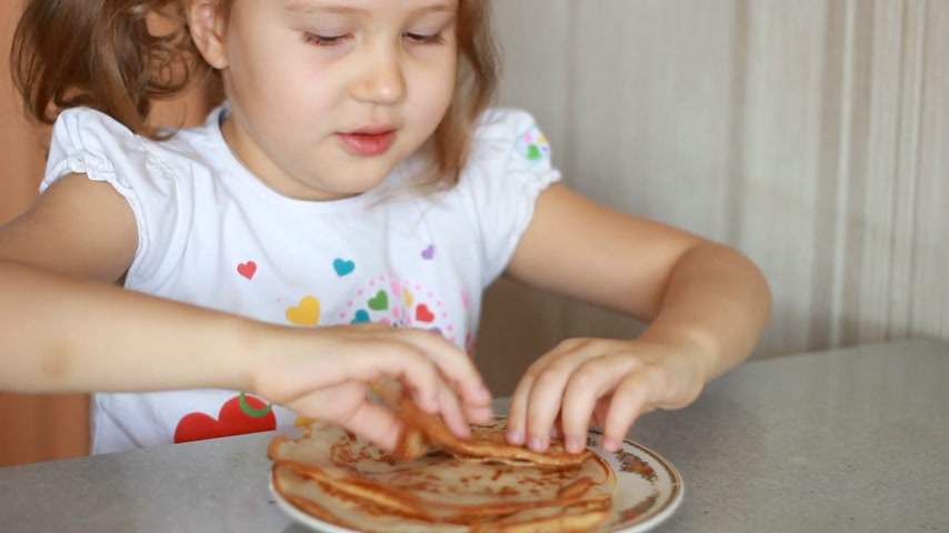 Baby girl eating pancakes. Child eating breakfast.