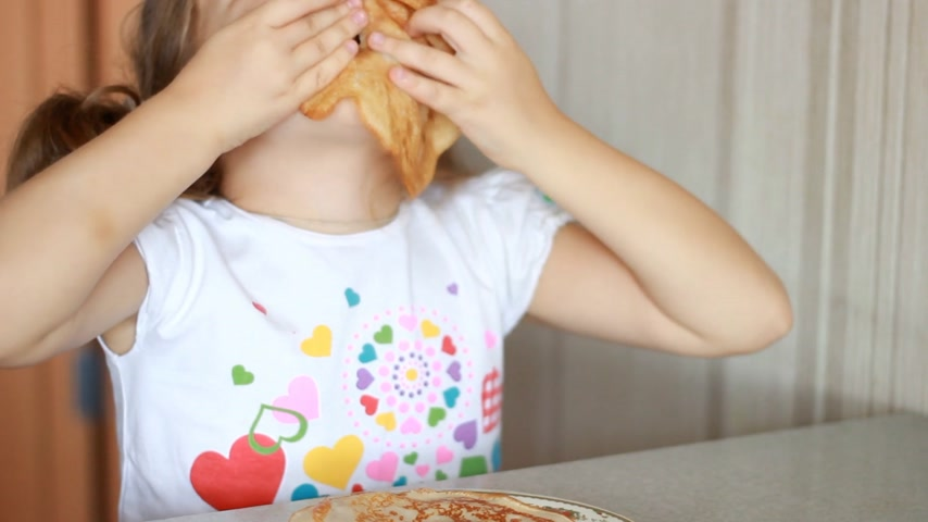 Baby girl eating pancakes. Child laughs and plays with pancake