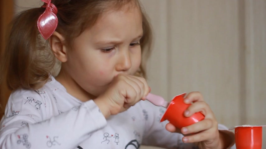 Child eating cottage cheese with a spoon. Baby girl eats dairy product yogurt. Portrait closeup. Stock Footage