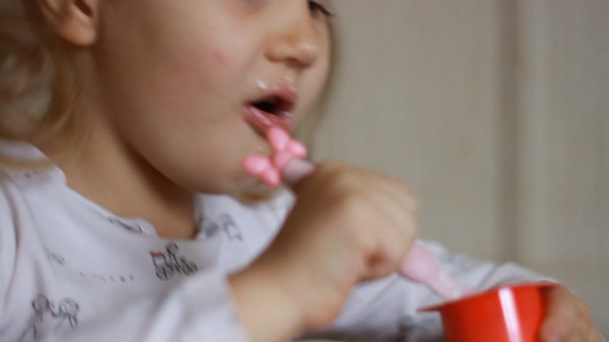 twaróg : Child eating cottage cheese with a spoon. Baby girl eats dairy product yogurt. Portrait closeup. Wideo