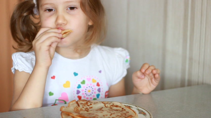 креп : Baby girl eating pancakes. Child eating breakfast.