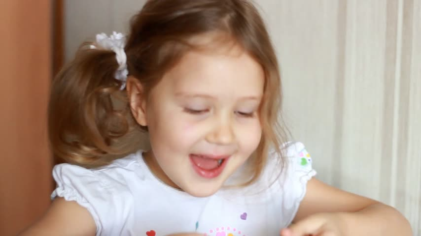 креп : Baby girl eating pancakes. Child laughs and plays with pancake