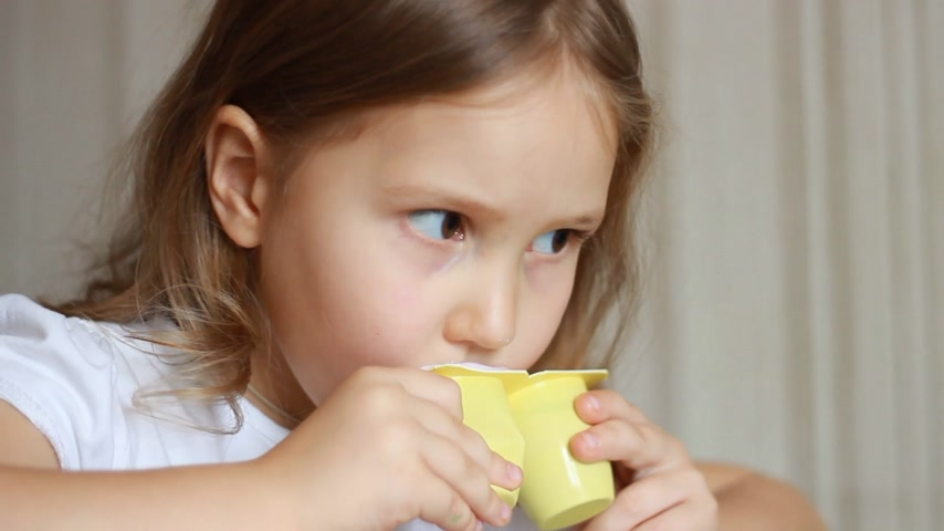 tvaroh : Baby girl eats dairy product yogurt. Child eating cottage cheese with a spoon. Portrait closeup