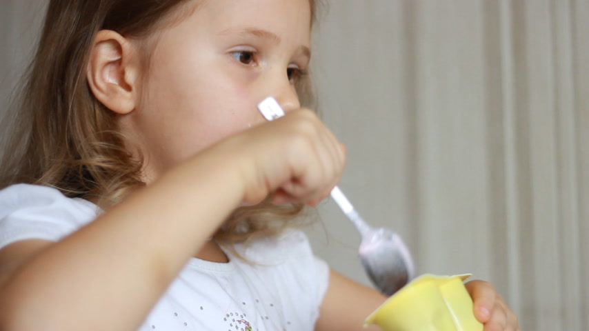 Baby girl eats dairy product yogurt. Child eating cottage cheese with a spoon. Portrait closeup
