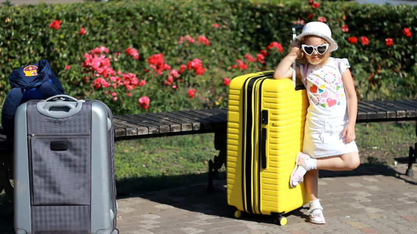 Child tourist with big yellow suitcase. Baby girl waiting for travel