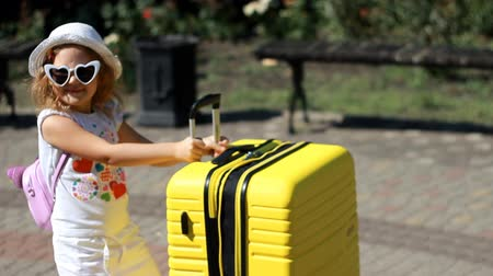 Heavy luggage. Child tourist with big yellow suitcase. Baby girl waiting for travel