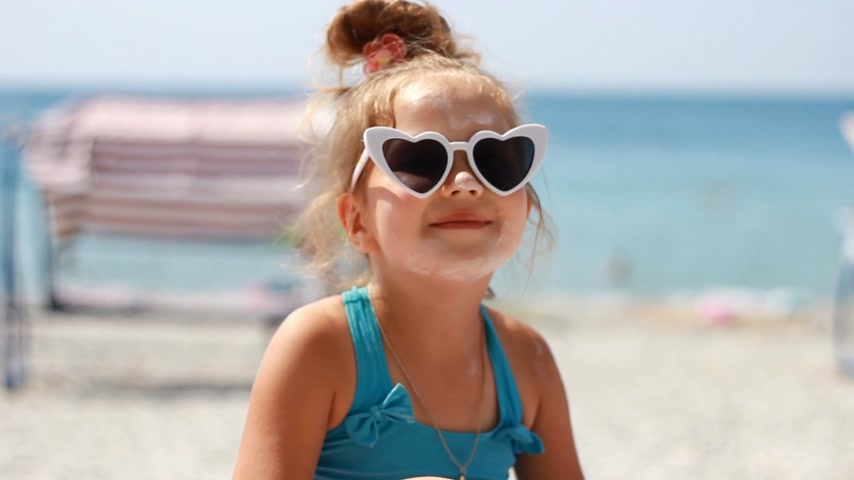 Child smearing sun cream fase. Sunburn. Suncream cream. Sunprotection cream. Cute baby girl in sunglasses sunbathes on a beach near the sea.